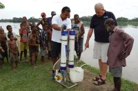 Sir Peter with Max showing the sepik river villagers how to use the new water pump he supplied
