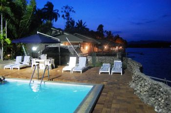 Madang Resort pool and rooms along sea front during night